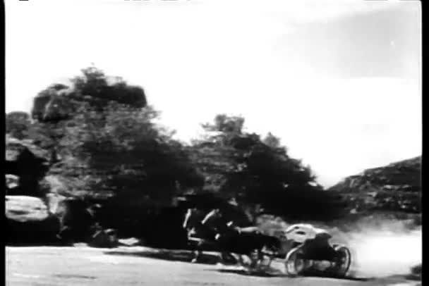 Long shot of galloping horses harnessed to an empty carriage on country road