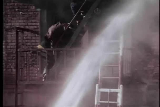 Hasiči záchrana oběti na požární schoditě hořící budovy
