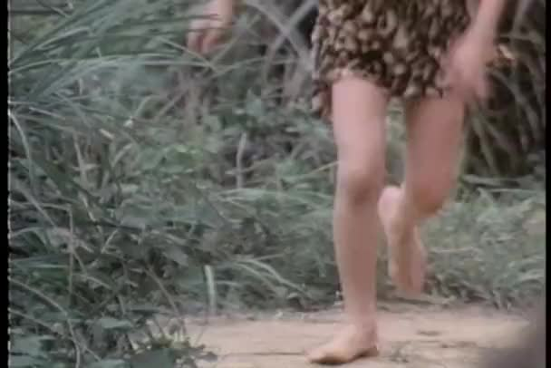 Low section of bare legged boy running through jungle