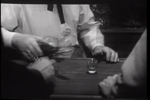 Bartender pouring shots for men at bar