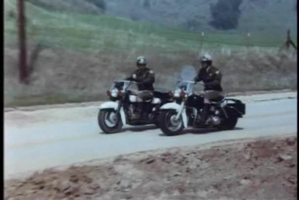 motocykl policie pronásleduje podezřelé na venkovské silnici