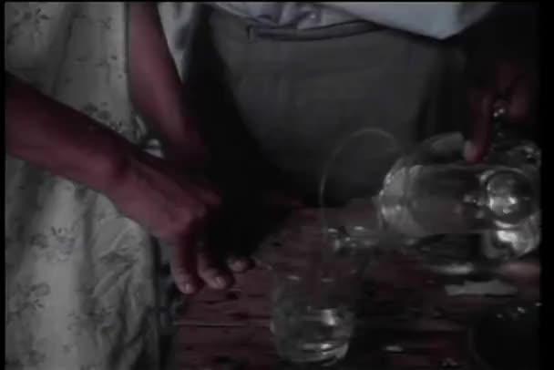 detail rukou nalití vody ze džbánu do skla
