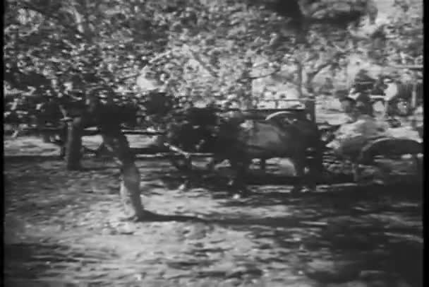 Villagers in horse carts and on foot traveling through forest