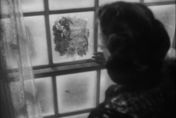 Woman looking out frosty window