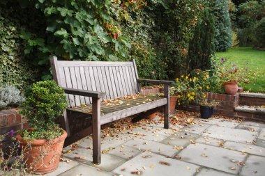 Garden bench on a traditional flagstone patio in autumn , fall stock vector