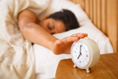 An Indian Asian woman wakes up and reaches to turn off a traditional alarm clock stock vector