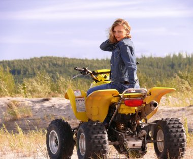Beautiful blonde on sport quadrocycle on background of the nature.