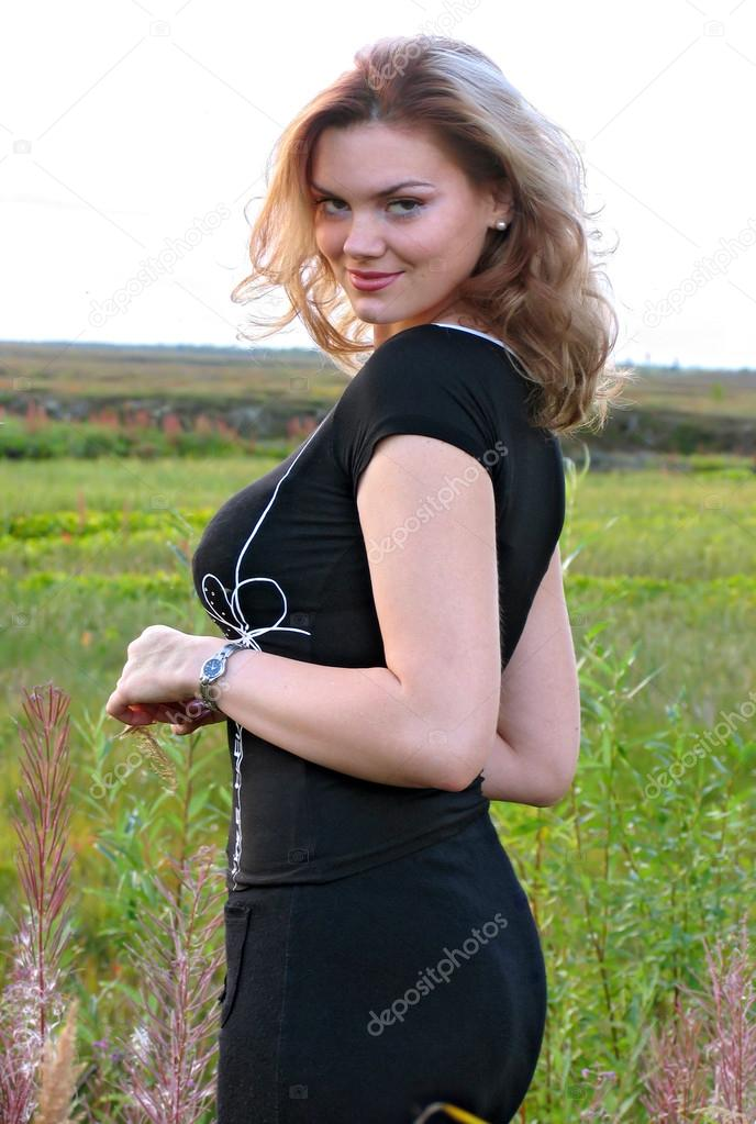 Beautiful girl with big breasts closeup on nature background.