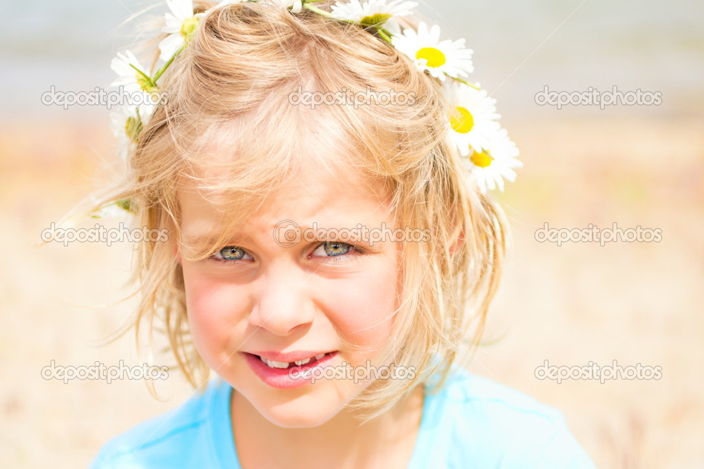 Pretty Little Blond Girl with a Crown of Daisies on the Beach
