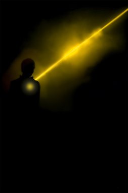 human silhouette in smoke lightened with bright ray