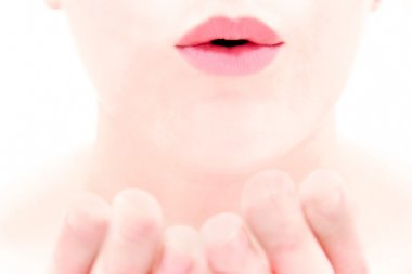 close up of female lips blowing a kiss over white
