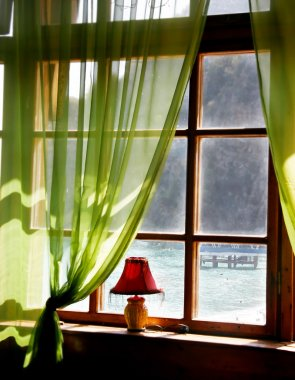 Wooden window with sea view in old hotel