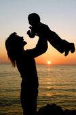 Fotografia madre, giocando con suo figlio sullo sfondo tramonto