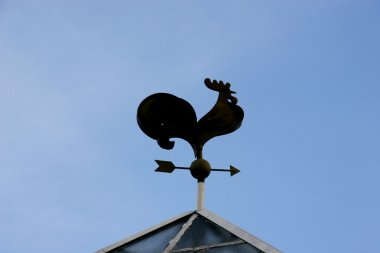 silhouette of weathercock over blue sky