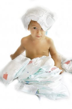 Baby boy playing with diapers over white