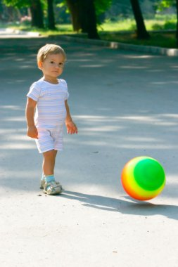 Baby boy with colorful ball walking in park