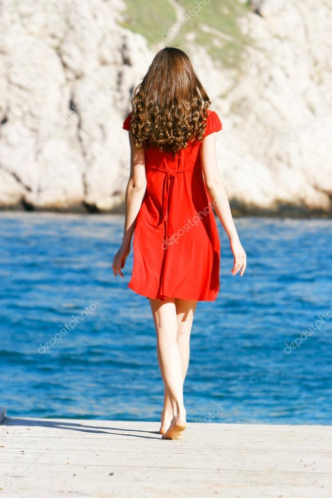 young girl in red dress on the sea