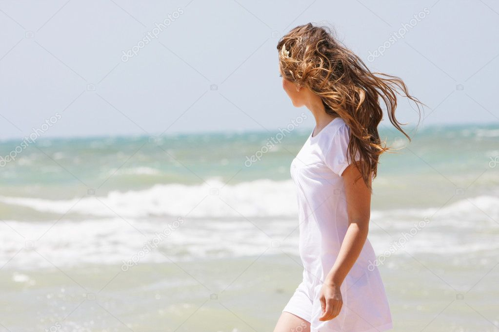 young happy girl walking on sea background