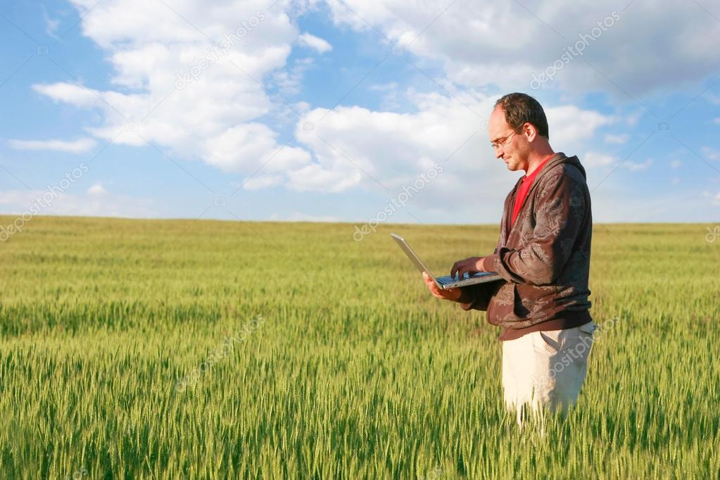 man with laptop in green field