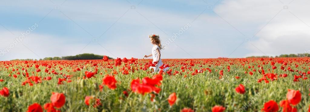 small girl in white dress running in poppy field