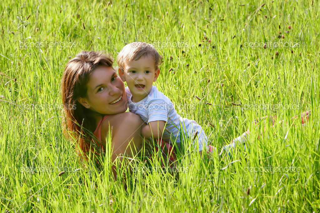 happy mother and son playing in grass