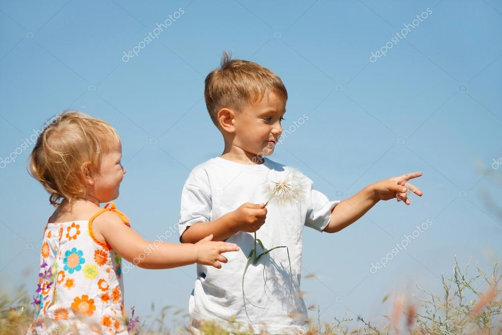 Two kids playing with big dandellions