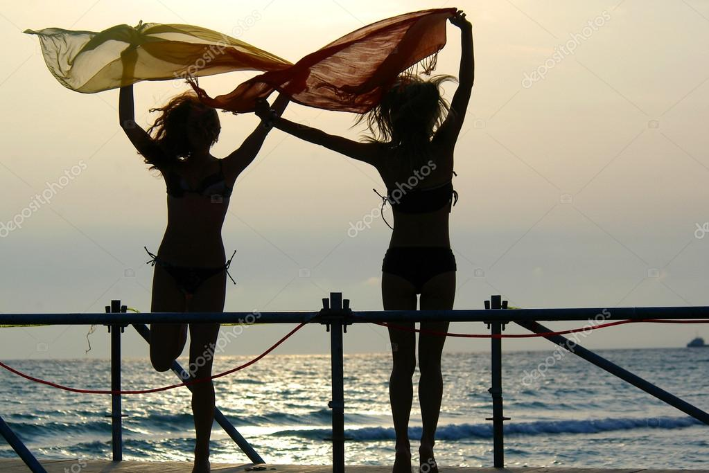 Silhouettes of two girls dancing with scarfs