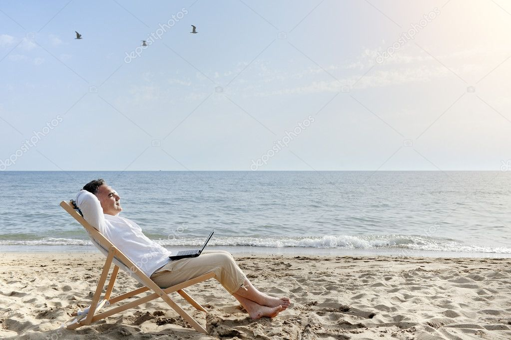 man with laptop computer relaxing on the beach