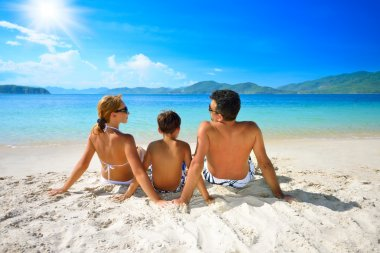 Happy family sunning on the beach on the background of the islan