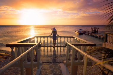 A woman in a hat looking at the romantic Caribbean sunset while