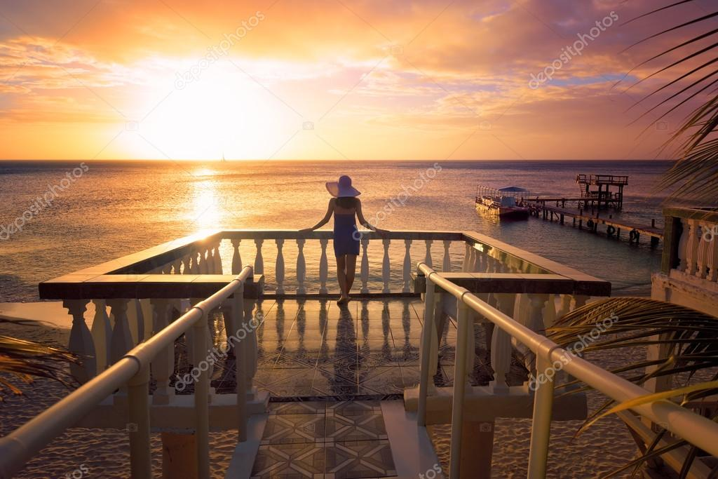 Фотообои A woman in a hat looking at the romantic Caribbean sunset while