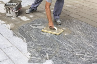 Worker grouting tiles