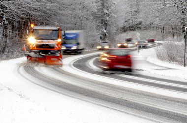 Winter road, snow plow and cars