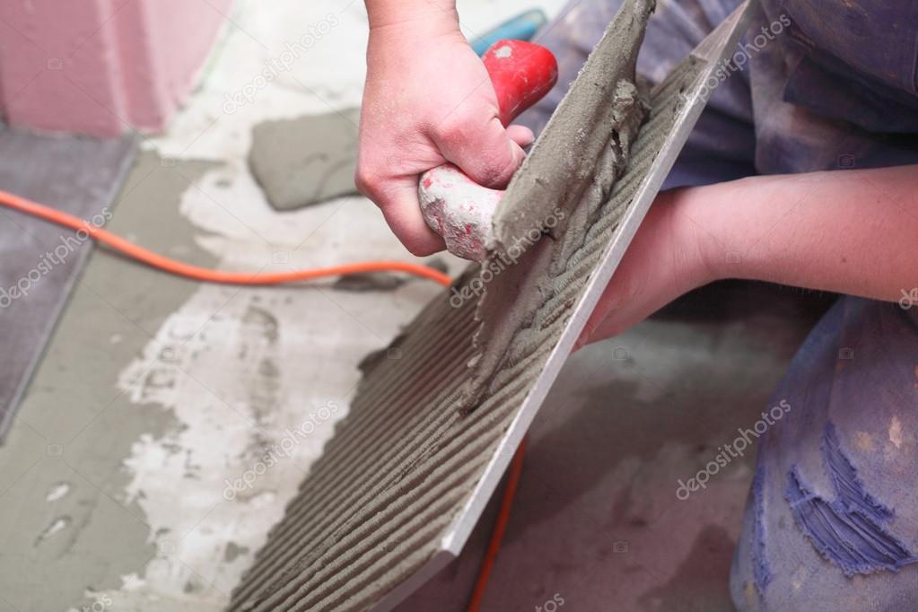 Operaio edile è affiancamento a casa piastrelle pavimento adesivo