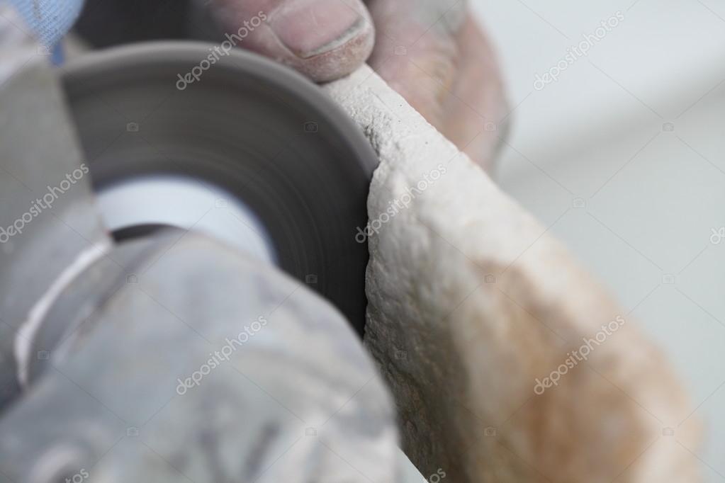 Operaio edile utilizzando una piastrella di taglio smerigliatrice di