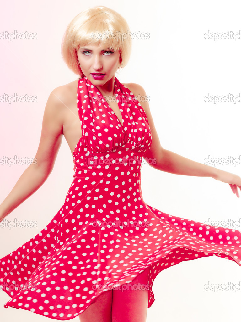 Beautiful pinup girl in blond wig and retro red dress dancing. Party ...
