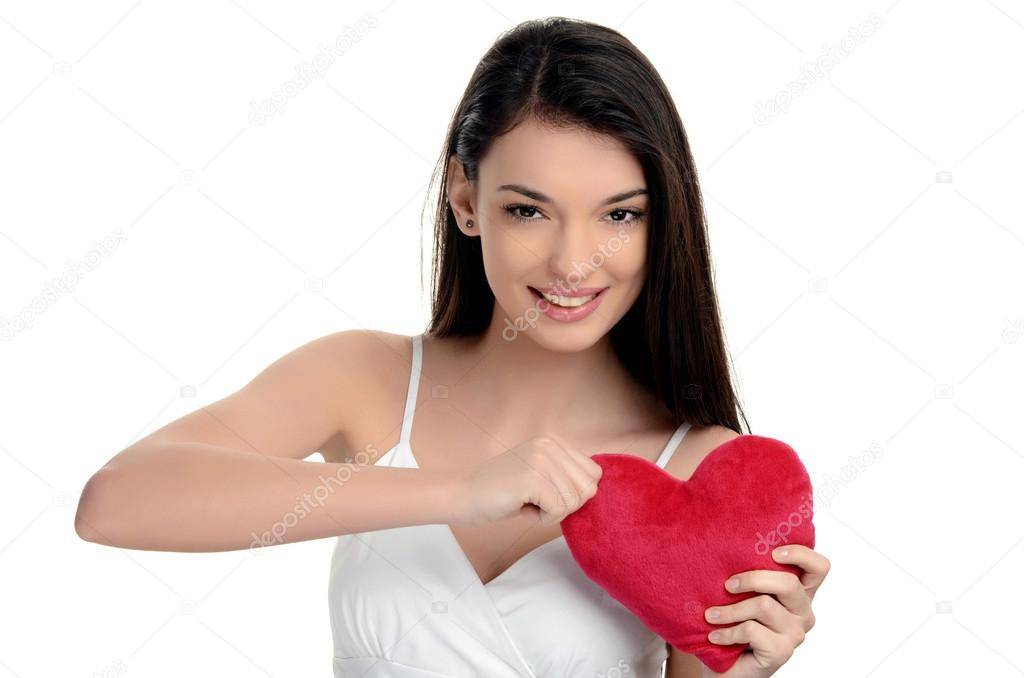 Beautiful brunette girl holding a red heart. Heart broken, loveless, angry on love. Woman tearing up a heart. Valentine day.