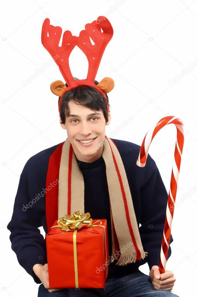 Joven guapo vestido para Navidad, renos cornudo. hombre que sostiene un regalo y un gran caramelo caña sonriendo — Foto de Stock