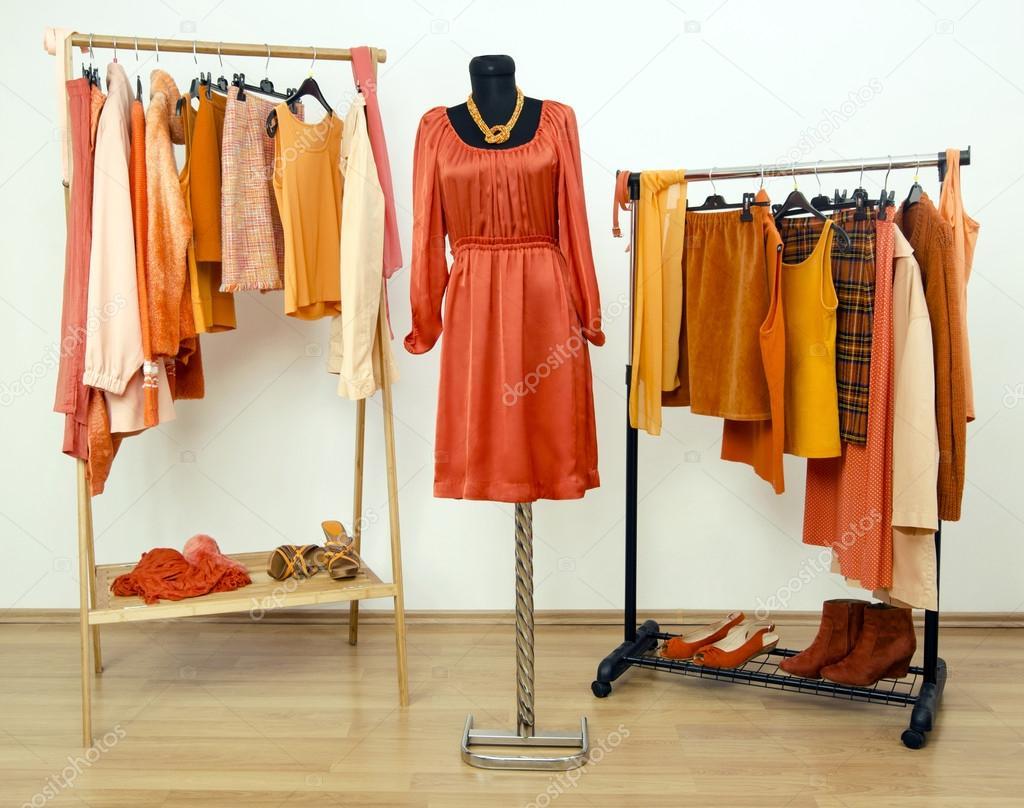 шафа з помаранчевих одязі влаштовується на вішалки і плаття на на ... aa539990f2e26
