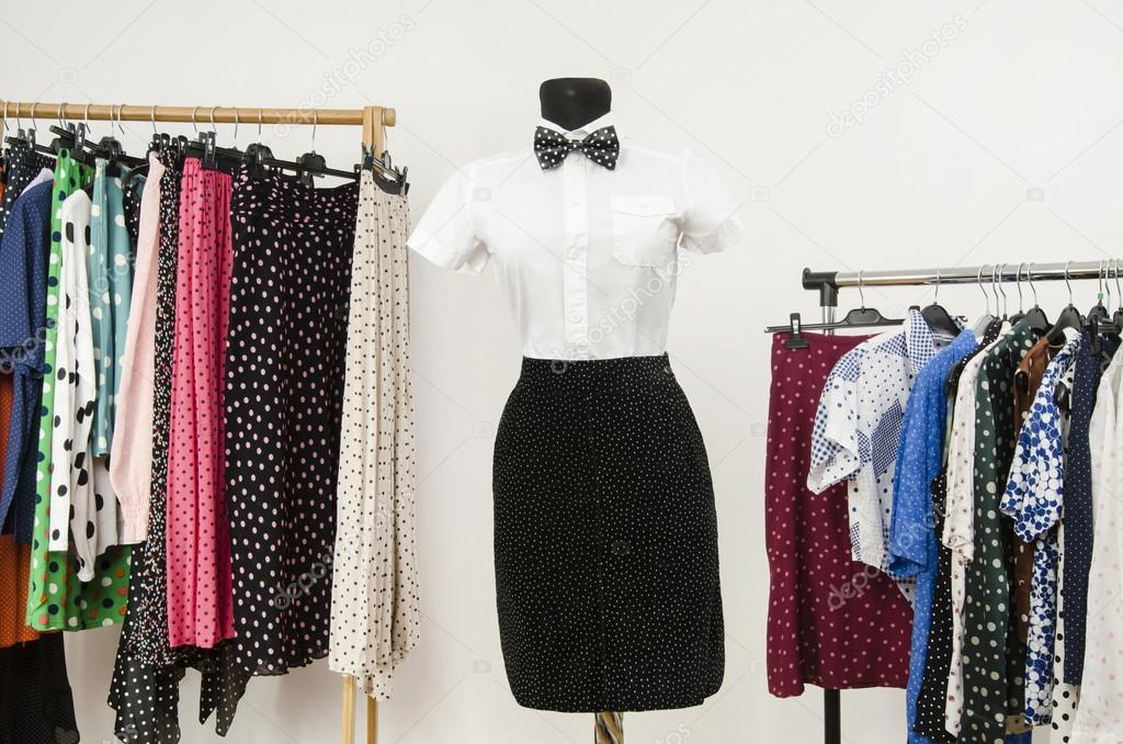 White shirt with bowtie and a black skirt on a mannequin. Wardrobe with polka dots clothes.