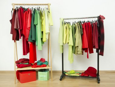Dressing closet with complementary colors red and green clothes arranged on hangers.