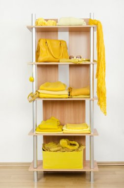 Yellow clothes nicely arranged on a shelf.