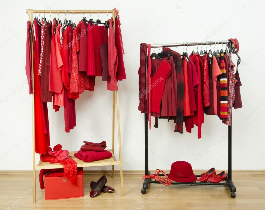 wardrobe with red clothes hanging on a rack nicely arranged u2014 stock photo