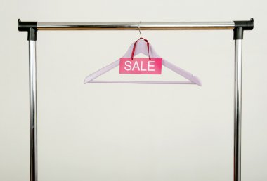 Empty hanger on a rack of clothes with the sale sign.