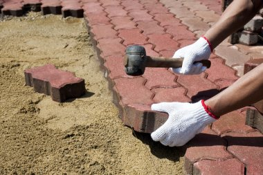A worker laying red concrete paving blocks.