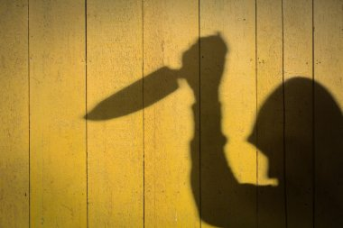Male Hand Shadow with Kitchen Knife, on wood wall