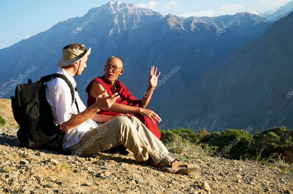 Tourist and monk in mountains