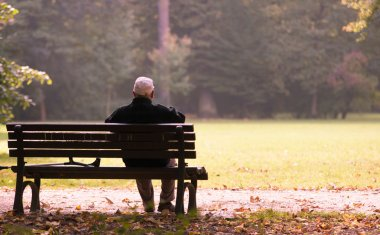 Old man sitting on a bench in autumn, autumn of life