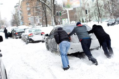 The guys are pushing a car stuck in the snow stock vector