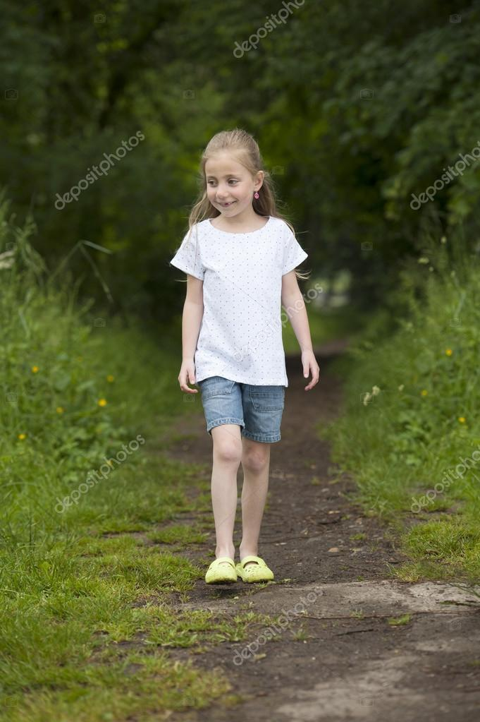 Summer holidays: Littel girl walking on a path in the woods